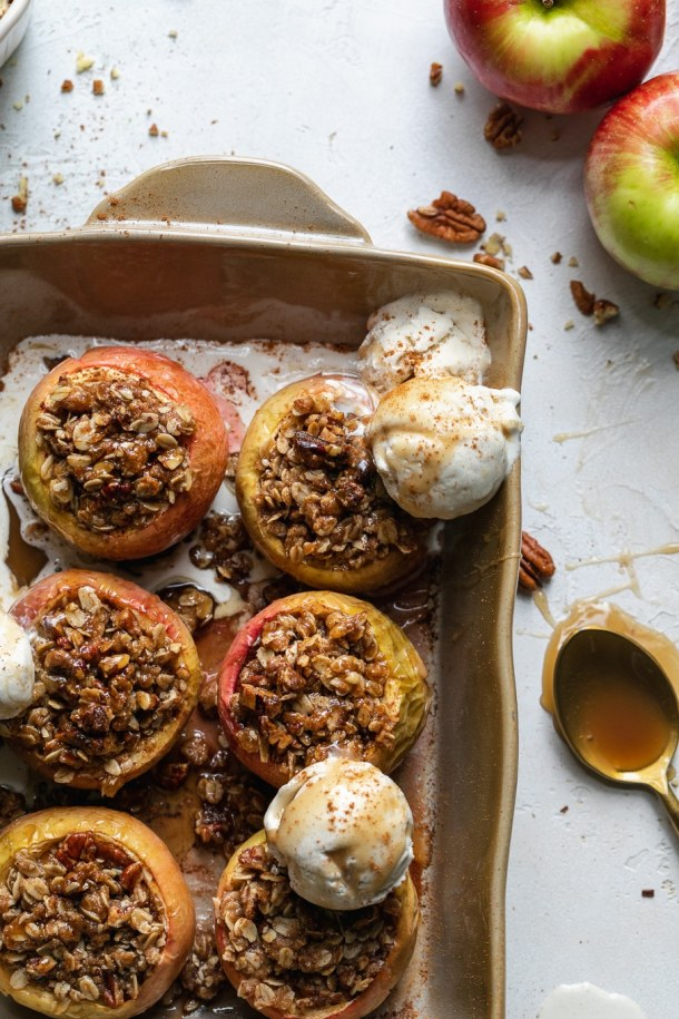Overhead close up shot of a casserole dish filled with baked apples and ice cream scoops