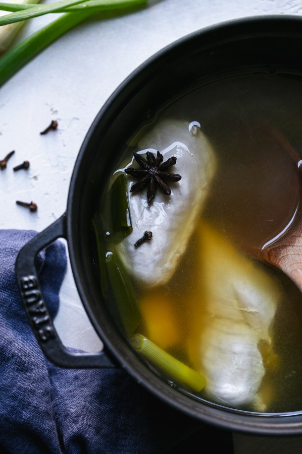 Close up shot of a black dutch oven filled with broth, chicken, and star anise