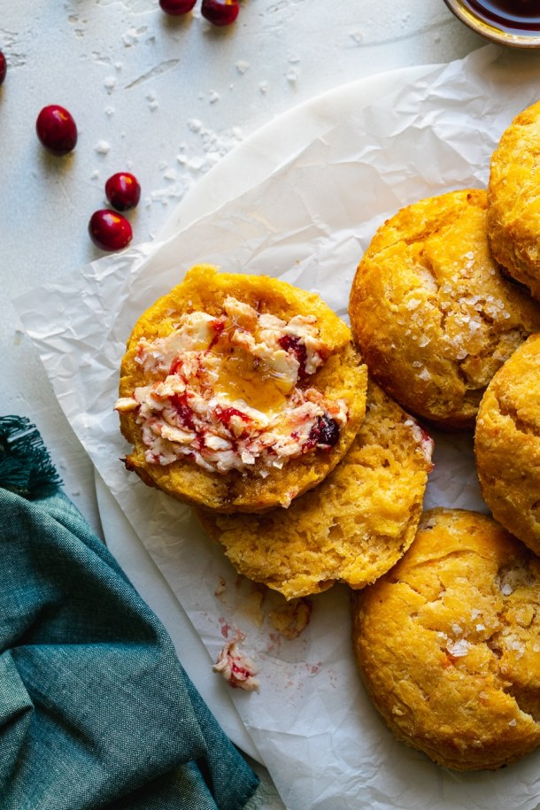 Overhead close up shot of a pile of sweet potato biscuits, one with cranberry butter on it