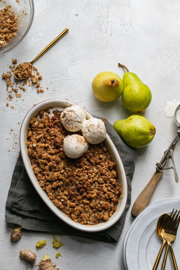 Overhead shot of a pear crisp with vanilla ice cream and a spoon digging in with pears next to it