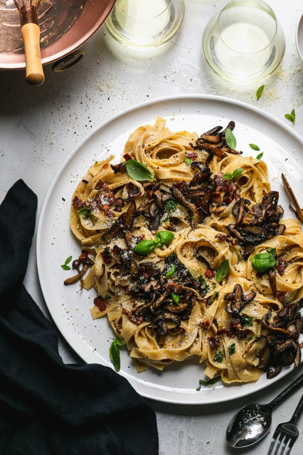 Overhead shot of pasta with mushrooms and herbs with glasses of white wine above the plate