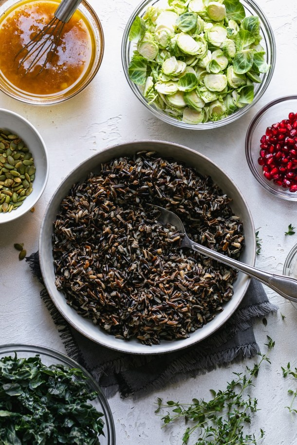 Overhead shot of a bowl of wild rice, surrounded by bowls of all other salad ingredients