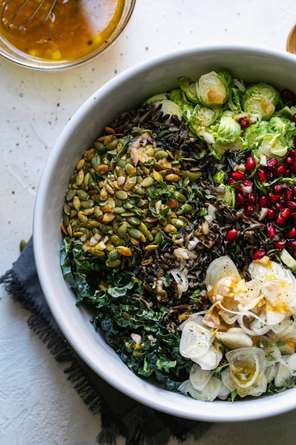 Overhead shot of a salad bowl filled with kale, pumpkin seeds, brussels, pomegranate, and shallots