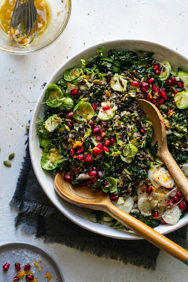 Overhead shot of a bowl of wild rice salad with wooden salad servers digging in