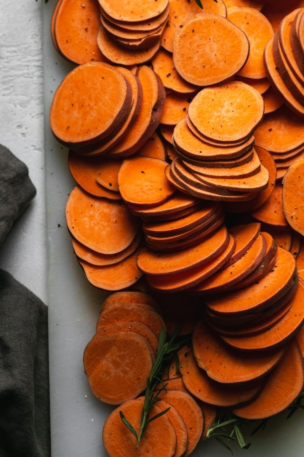Overhead shot of a pile of thinly sliced sweet potatoes