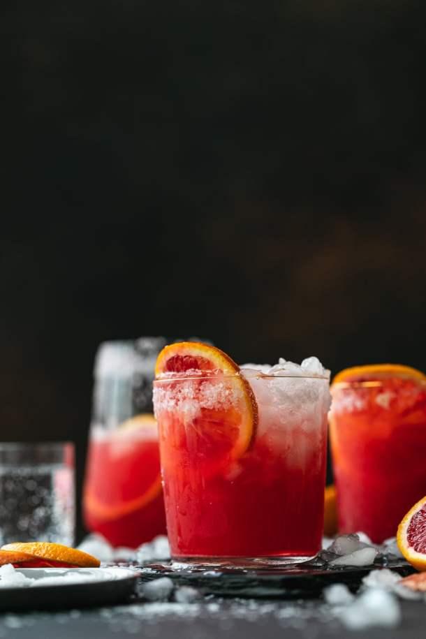 Straight on shot of blood orange paloma cocktails against a dark background