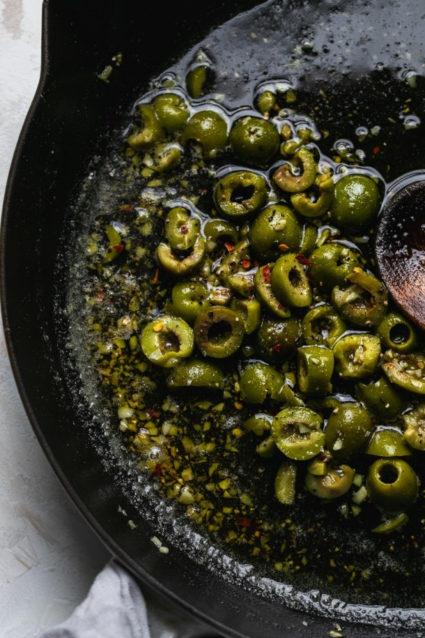 Shot of sautéed olives in a skillet
