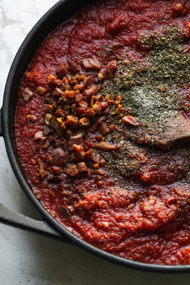 Close up shot of a skillet filled with tomato sauce, pancetta, and spices