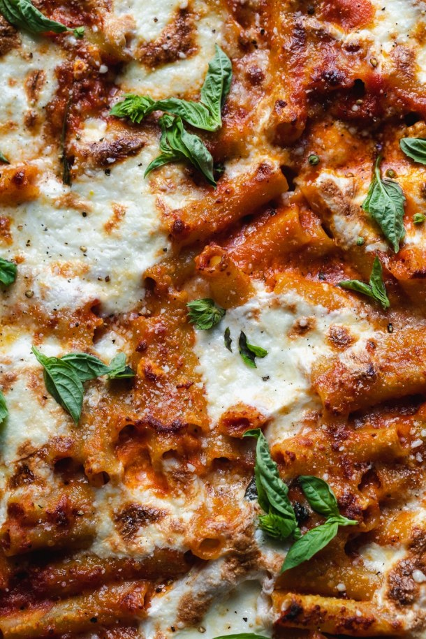 Super close up shot of baked ziti with basil leaves