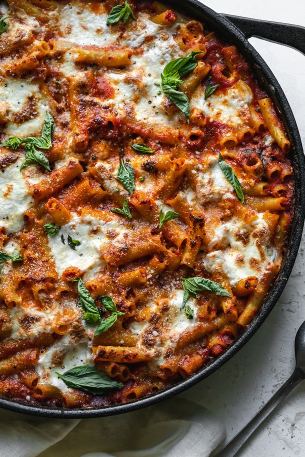 Overhead shot of a skillet of baked ziti garnished with basil