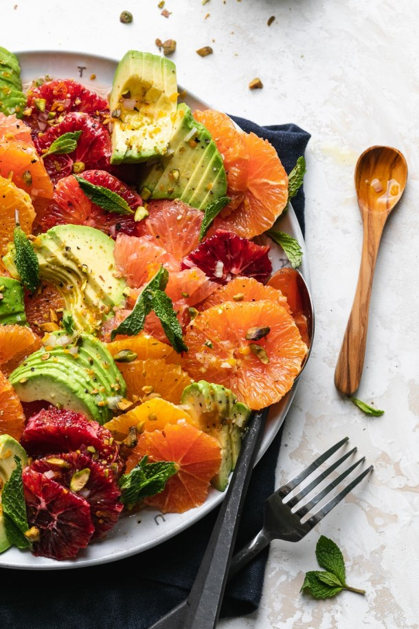 Close up shot of sliced winter citrus and avocado on a large plate
