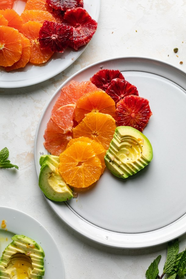 Overhead shot of sliced grapefruit, oranges, blood oranges, and avocado on a white plate