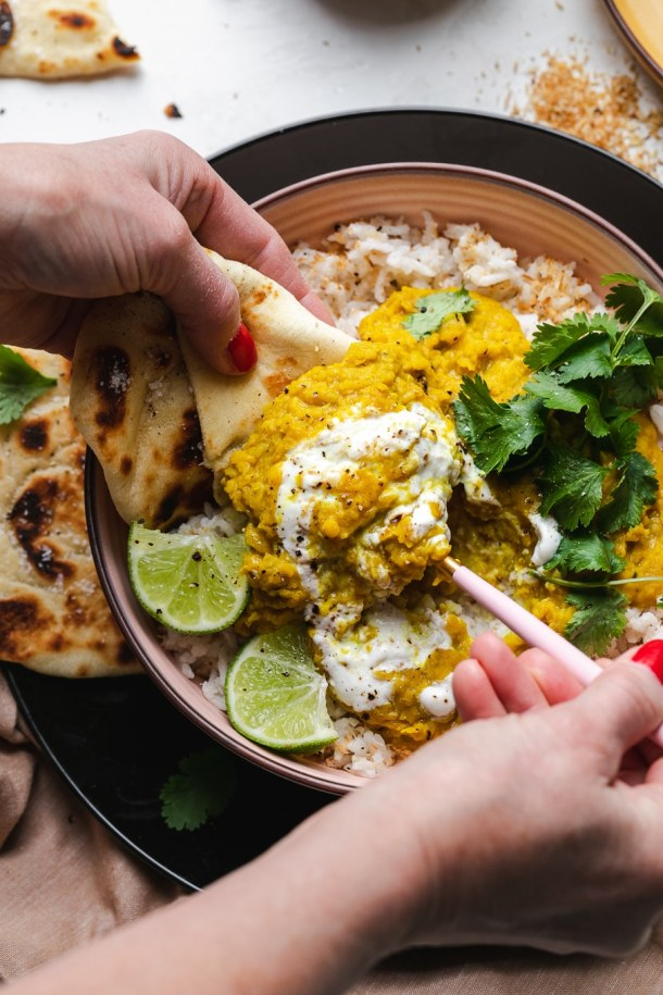 Overhead shot of hands scooping lentil dal and rice on naan bread