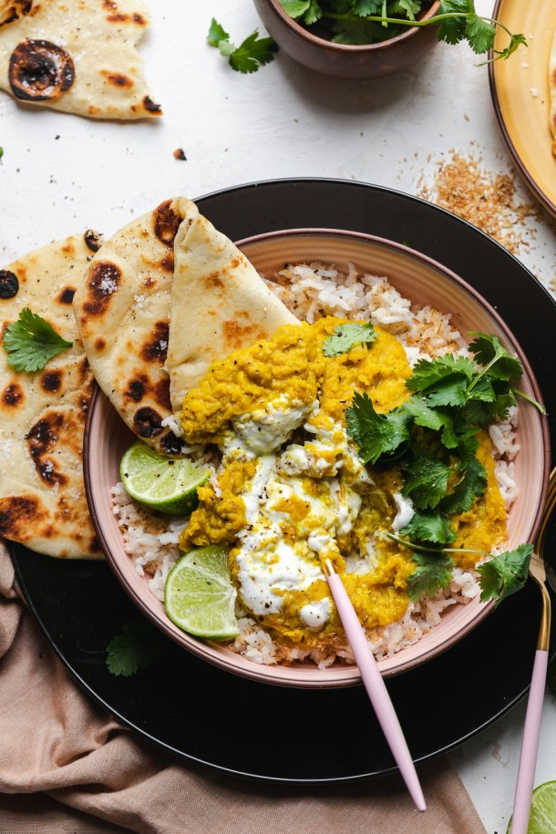 Overhead shot of a bowl with rice, lentil dal, cilantro, lime wedges, and naan
