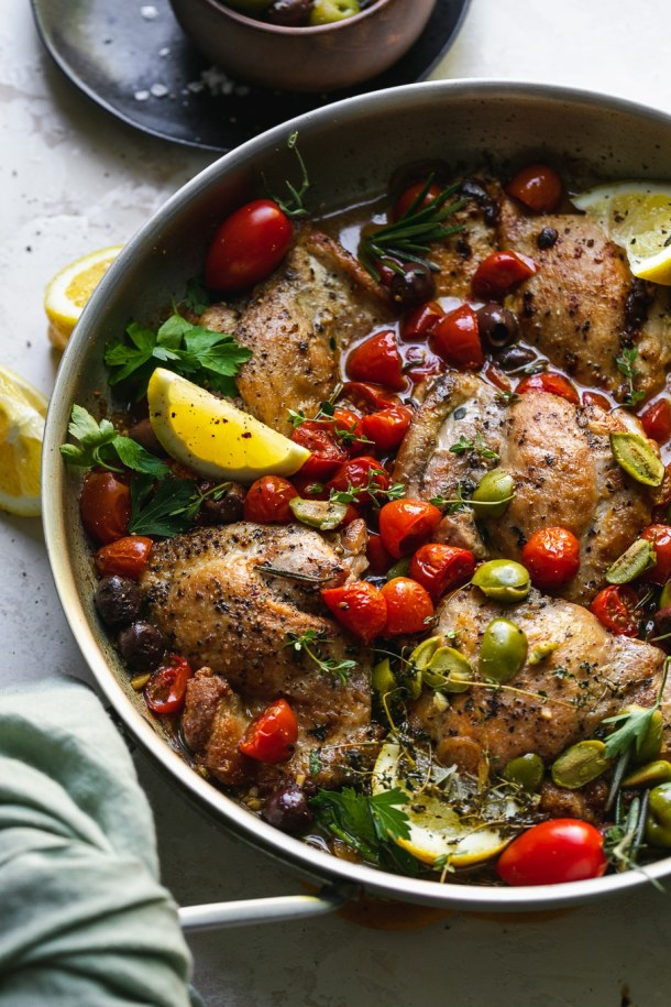Close up shot of a skillet filled with chicken, tomatoes, olives, herbs, and lemon
