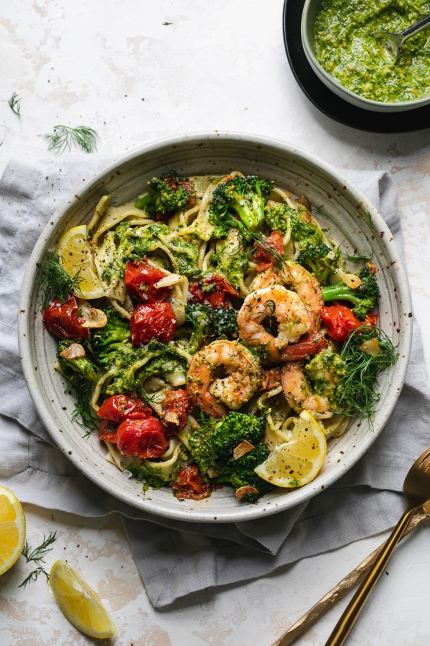 Overhead shot of a bowl of pasta with shrimp, pesto, broccoli, and tomatoes