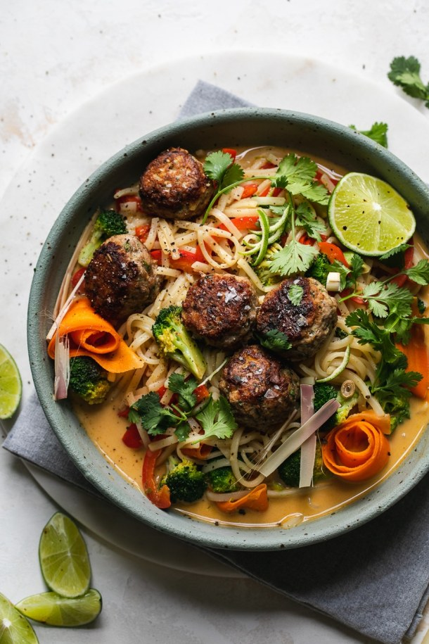 Overhead shot of a bowl of rice noodle stir fry with meatballs