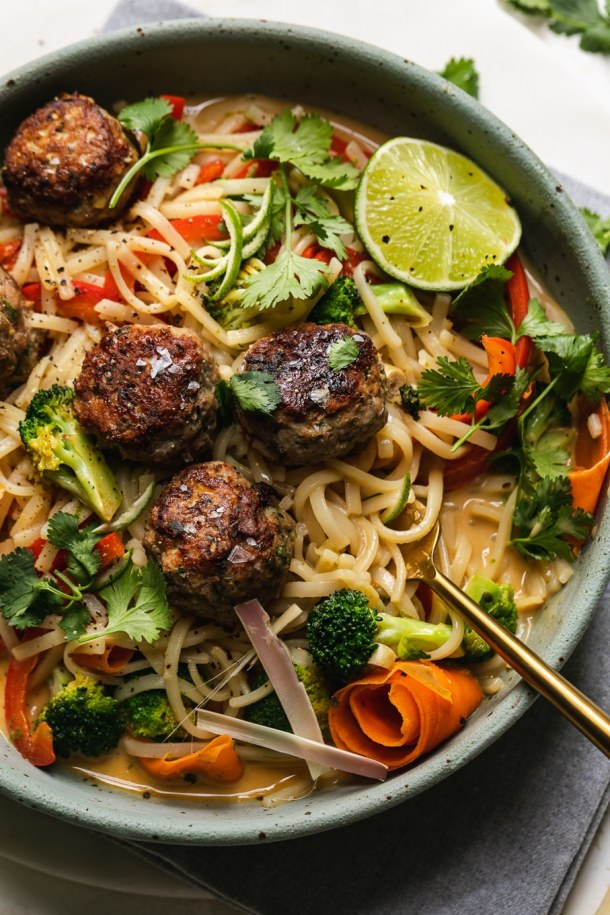 Close up shot of a bowl of rice noodles, veggies, and meatballs with a fork in the bowl