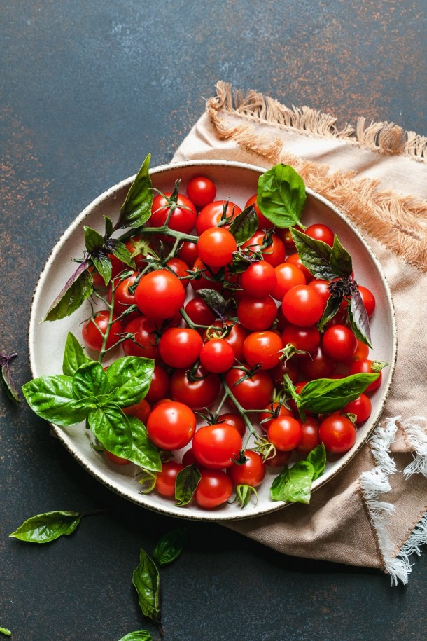 Overhead shot of a bowl of cherry tomatoes and basil