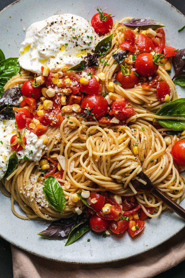 Overhead close up shot of pasta with tomatoes and corn