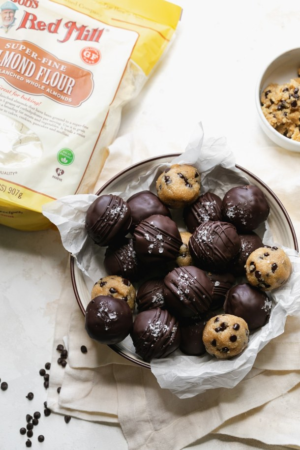Overhead shot of chocolate covered cookie dough bites next to bag of almond flour