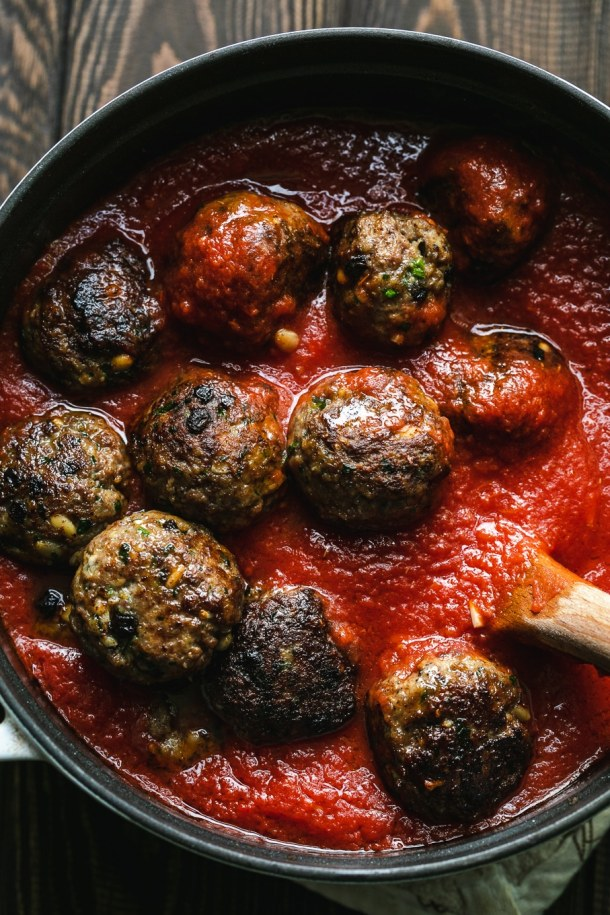 Overhead shot of a pot of tomato sauce with Sicilian meatballs being stirred in