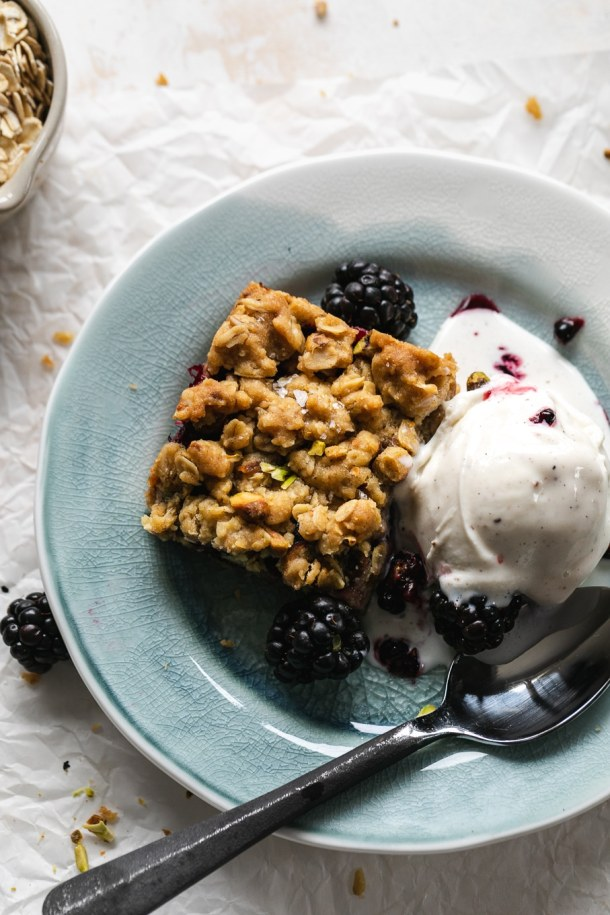 Overhead close up shot of a blackberry crumble bar with a scoop of vanilla ice cream