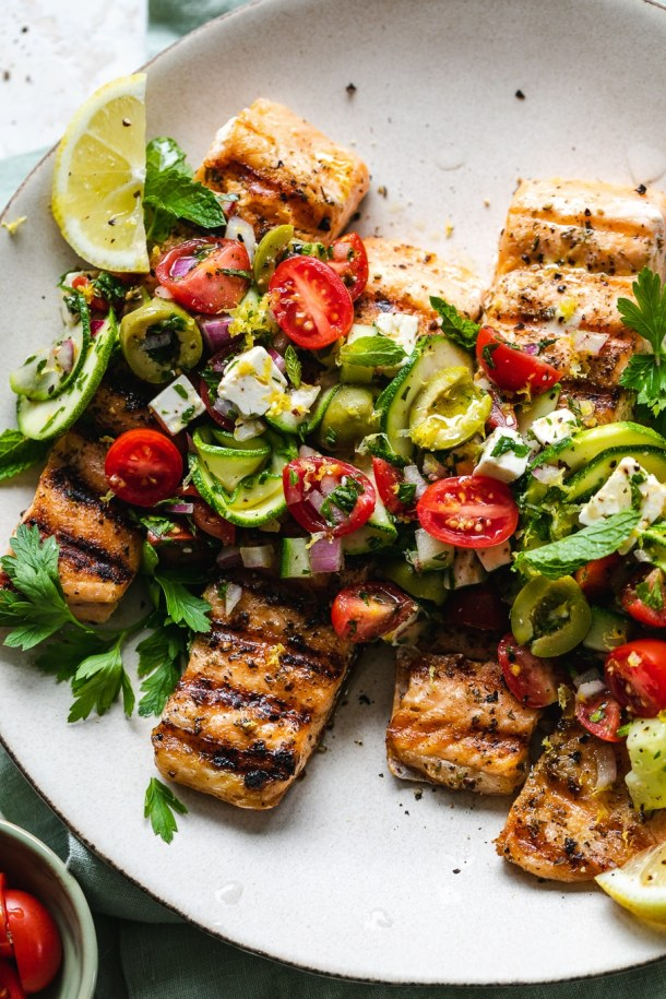 Close up shot of grilled salmon topped with greek salad