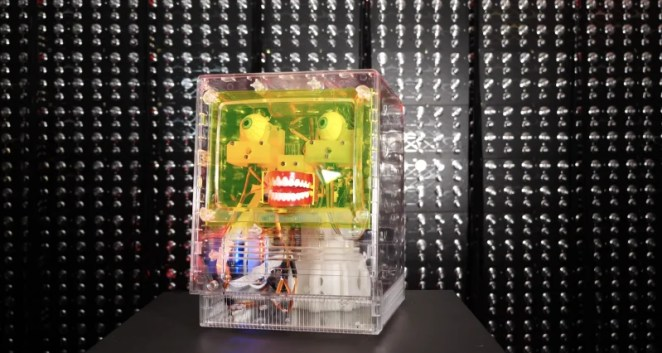 furby facial recognition robot in a clear case in front of a dark background