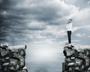 Businessman thinking at the edge of a cliff with the sea on the background