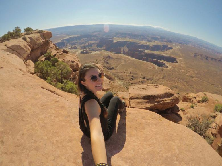girl sitting on edge of lookout at canyonlands national park