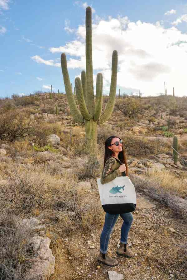 Girl wearing Whale Shark Tote Bag in the desert next to saguaro cactus
