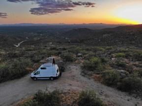 van life girl watching sunset in desert