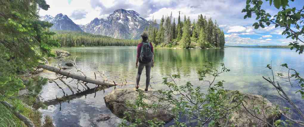 girl standing in front of string lake with views of tetons