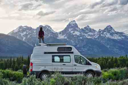 girl on van in front of grand teton mountains