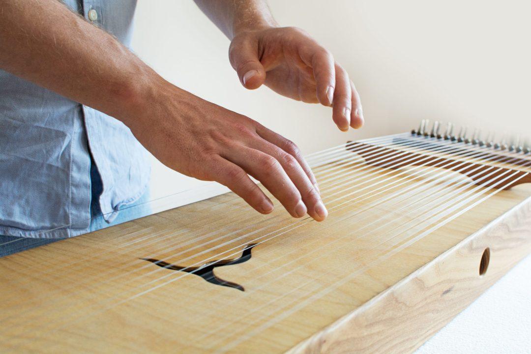 die Finger streichen die Saiten an und erzeugen ein harmonisches Klangfeld