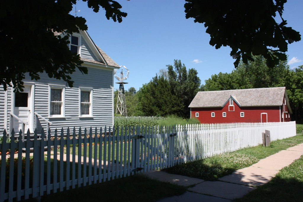farm scene with picket fence and red barn