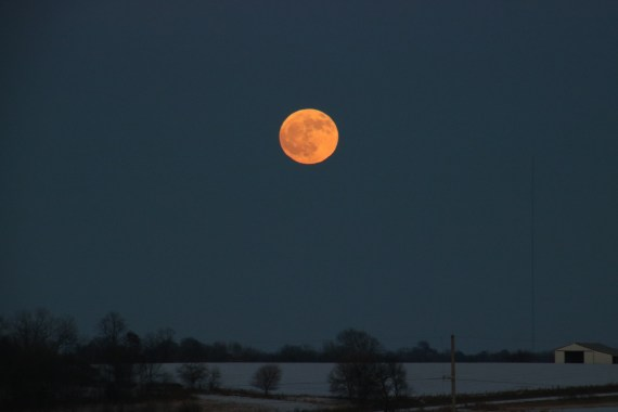 full moon above farm field