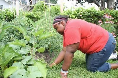 Ciara Jones weeds the garden despite a gardening injury: a hurt ankle.