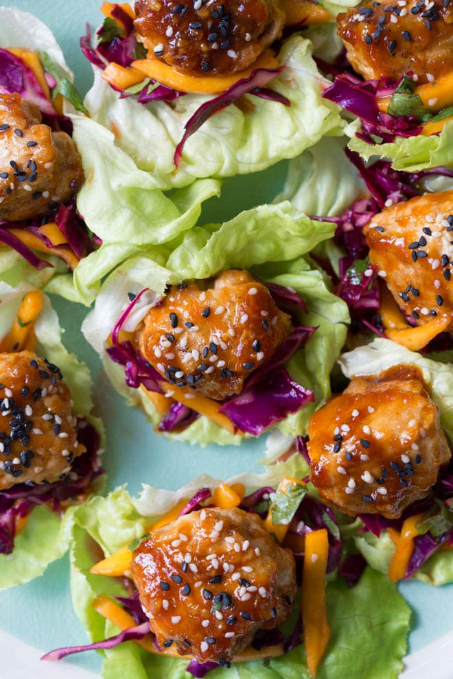 Wrap saucy chicken meatballs and fresh mango slaw with crunchy butter lettuce to create these Asian Chicken Meatball Lettuce Wraps with Mango Slaw! Enjoy them for lunch, dinner or as an appetizer. #chicken #meatballs #dinner #lunch #appetizer #asian #healthy #recipe #mango #cabbage