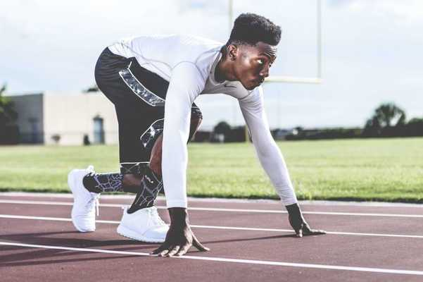 Leichtathletik Start - Foto: Pexels / nappy / https://www.pexels.com/photo/man-wearing-white-sweater-and-black-shorts-about-to-run-936094/