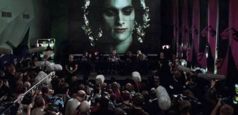 Lestat, on a jumbotron, telling reporters about how he's a vampire.