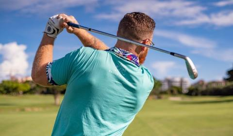 man playing golf on sunny day