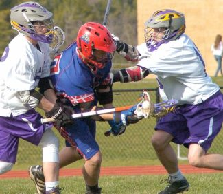 Voorheesville's Gabriel DeFreest-Rondeau, right, and Ian Owens, right, surround Maple Hill's Nick Morris during the first quarter of a Colonial Council game Wednesday, April 13. Rob Jonas/Spotlight