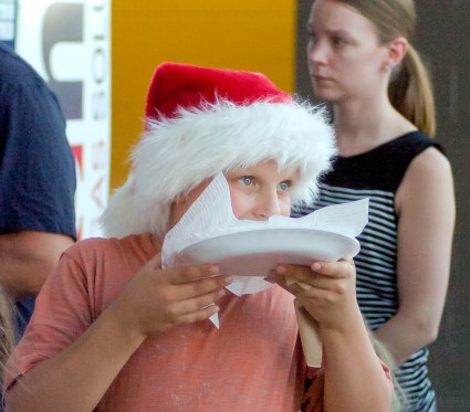 """A young fan sporting a Santa hat enjoys some fried dough during the Tri-City ValleyCats """"Christmas in July"""" game against Connecticut Thursday, July 14. Rob Jonas/Spotlight"""