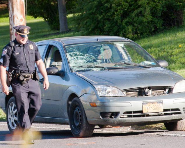 A Colonie police officer walks by a 2005 Ford on Albany Street. (Photo by Jim Franco/Spotlight News)