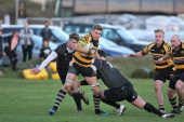 John Dibb tries to release the ball before being tackled