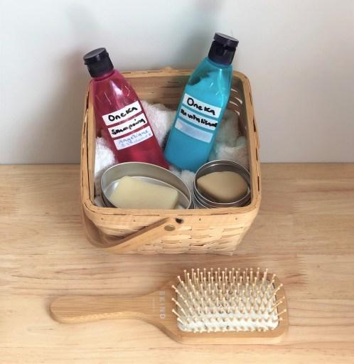 Shampoings et revitalisants solides et en vrac, dans une boîte en bois, avec une brosse en bambou posée devant.