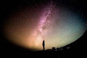 Personne regardant vers l'horizon, sur fond de galaxie étoilée.