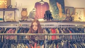 Jeune femme cherchant parmi des portoirs de vêtements, dans une friperie.